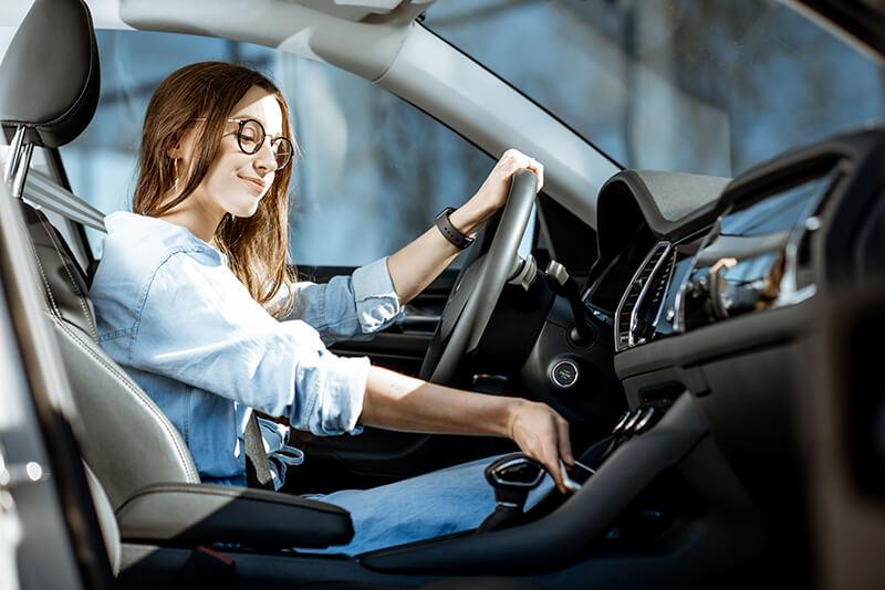 Chica en un coche que va a conducir eficientemente.
